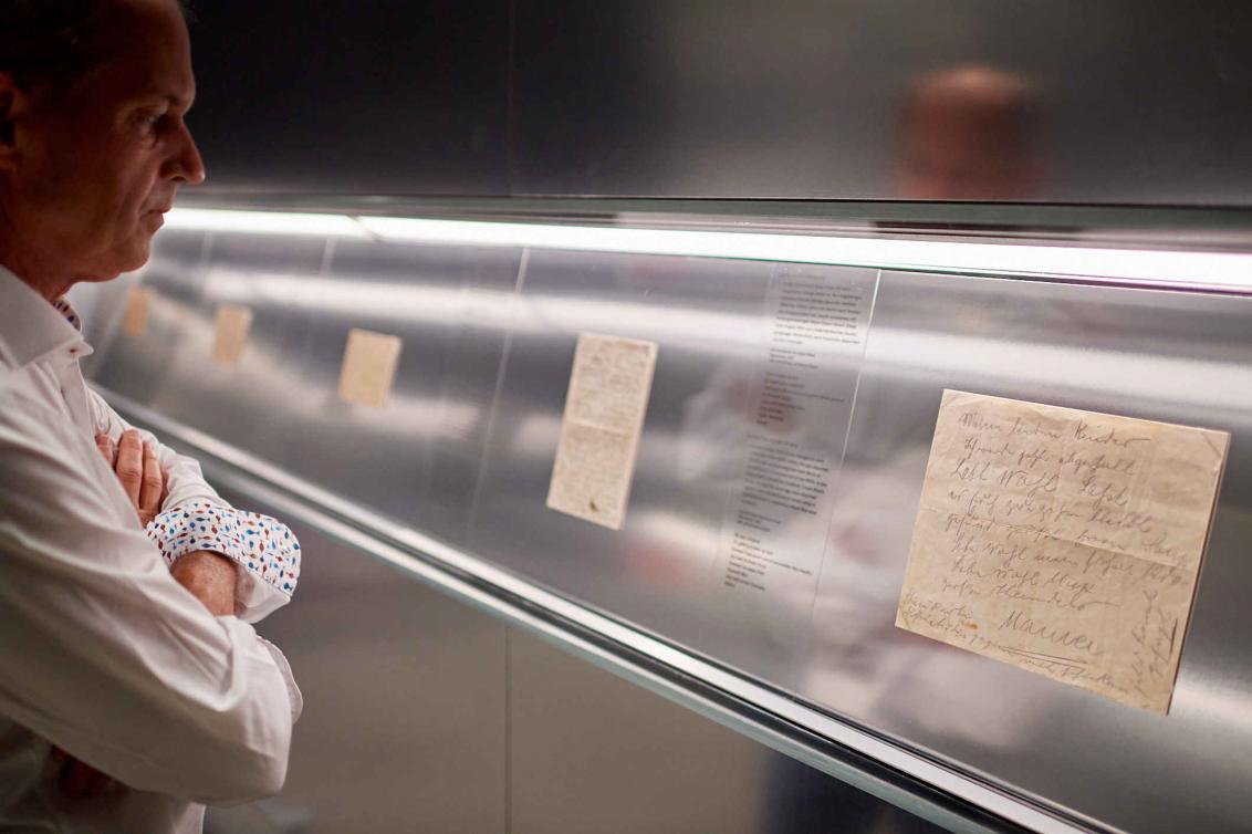 Ein Mann steht vor einer Vitrine mit einem alten Brief