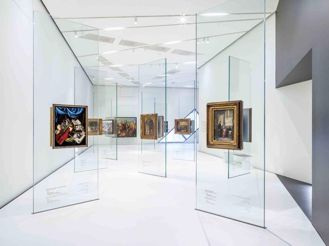 Weißer Raum, Glasstelen, an denen Gemälde hängen