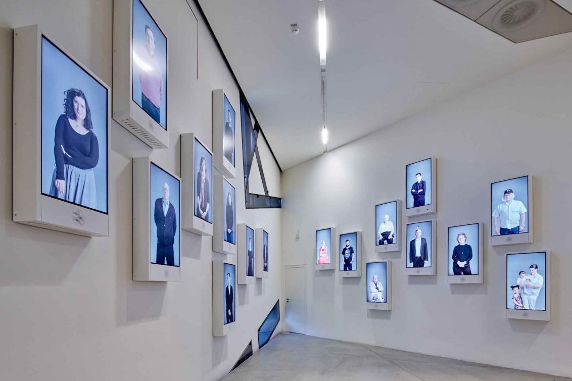 Wand mit mehreren Bildschirmen, auf denen Personen sind
