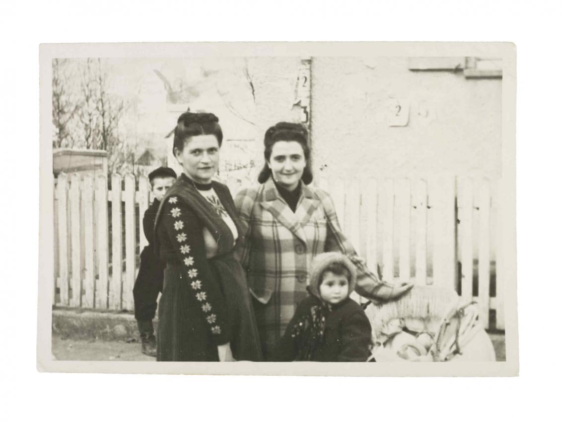 Foto von zwei Frauen und zwei Kindern vor einem Lattenzaun