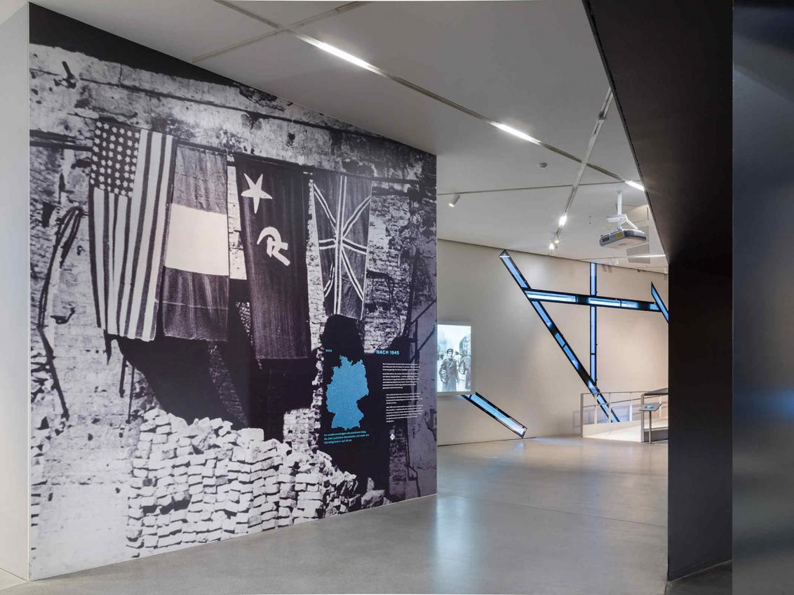 An einer Wand ein altes Foto von einer amerikanischen, einer französischen, einer sowjetischen und einer britischen Fahne