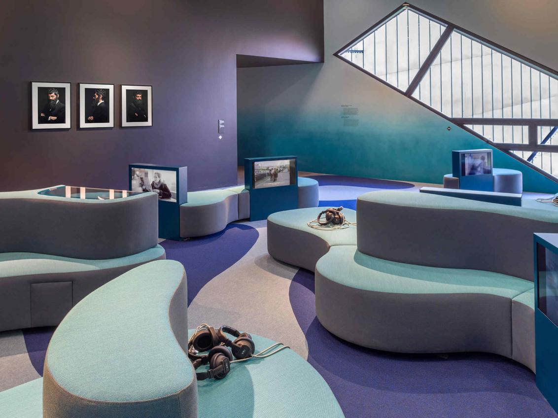 Raum mit Farbverlauf von lila zu türkisblau, Sofas, Kopfhörer, Bildschirme