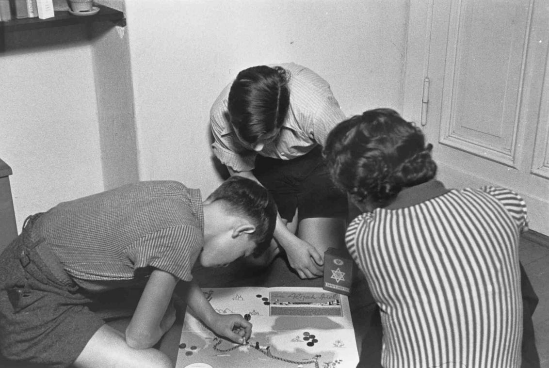 Schwarz-Weiß-Fotographie mit einer Frau und zwei Schülern, die ein Brettspiel spielen