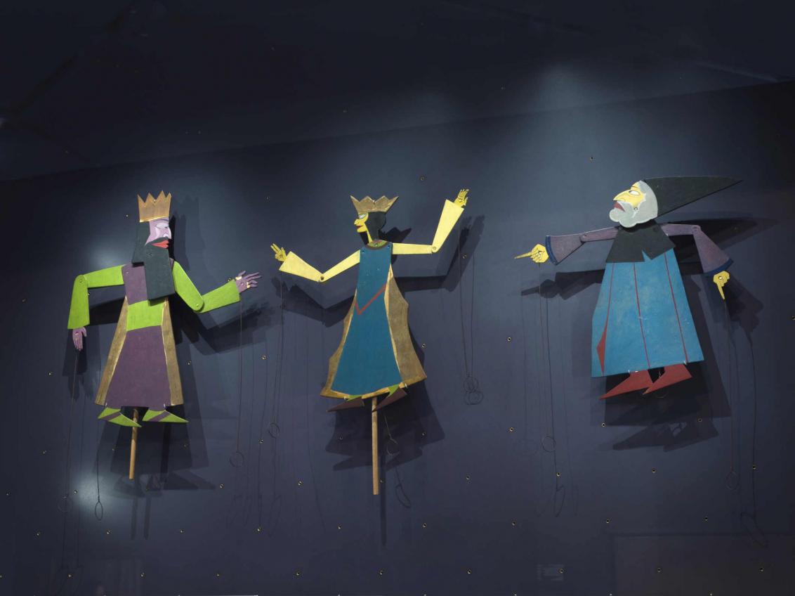 Drei Figuren an jeweils einem Stab befestigte Figuren, zwei mit Krone, einer mit einem spitzen Hut