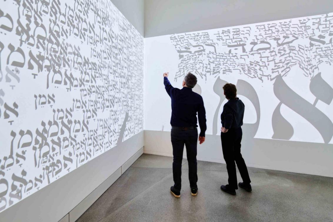 Große Leinwand mit hebräischen Buchstaben vor der zwei Personen stehen
