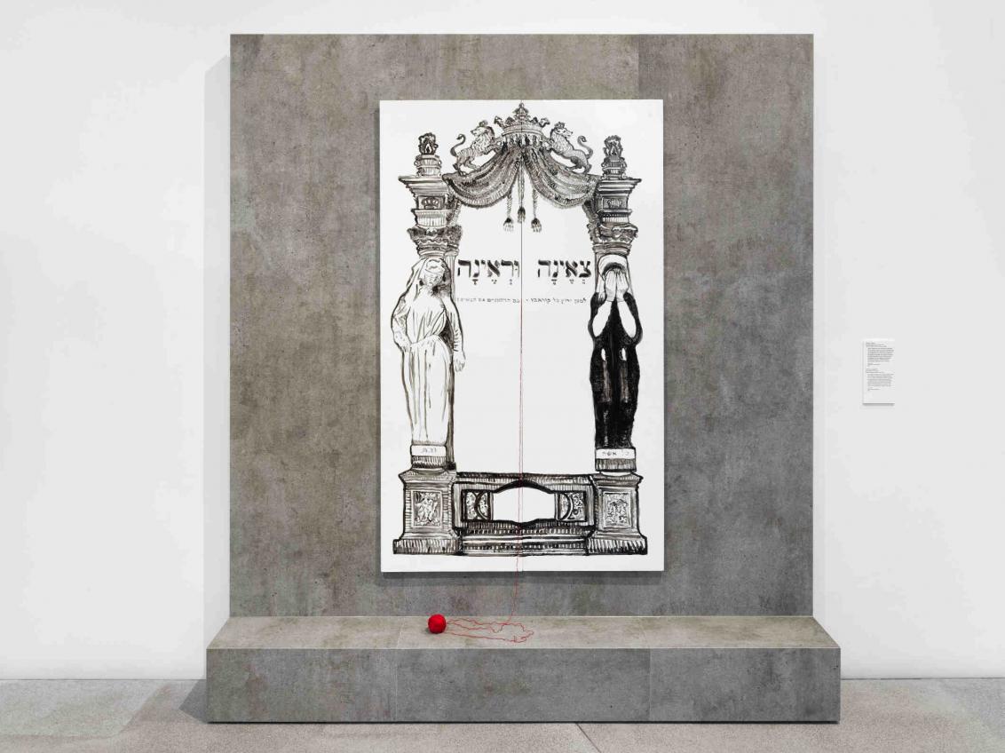 Ausstellungsmöbel aus Beton mit einem schwarz-weiß Bild und einem roten Wollknäuel