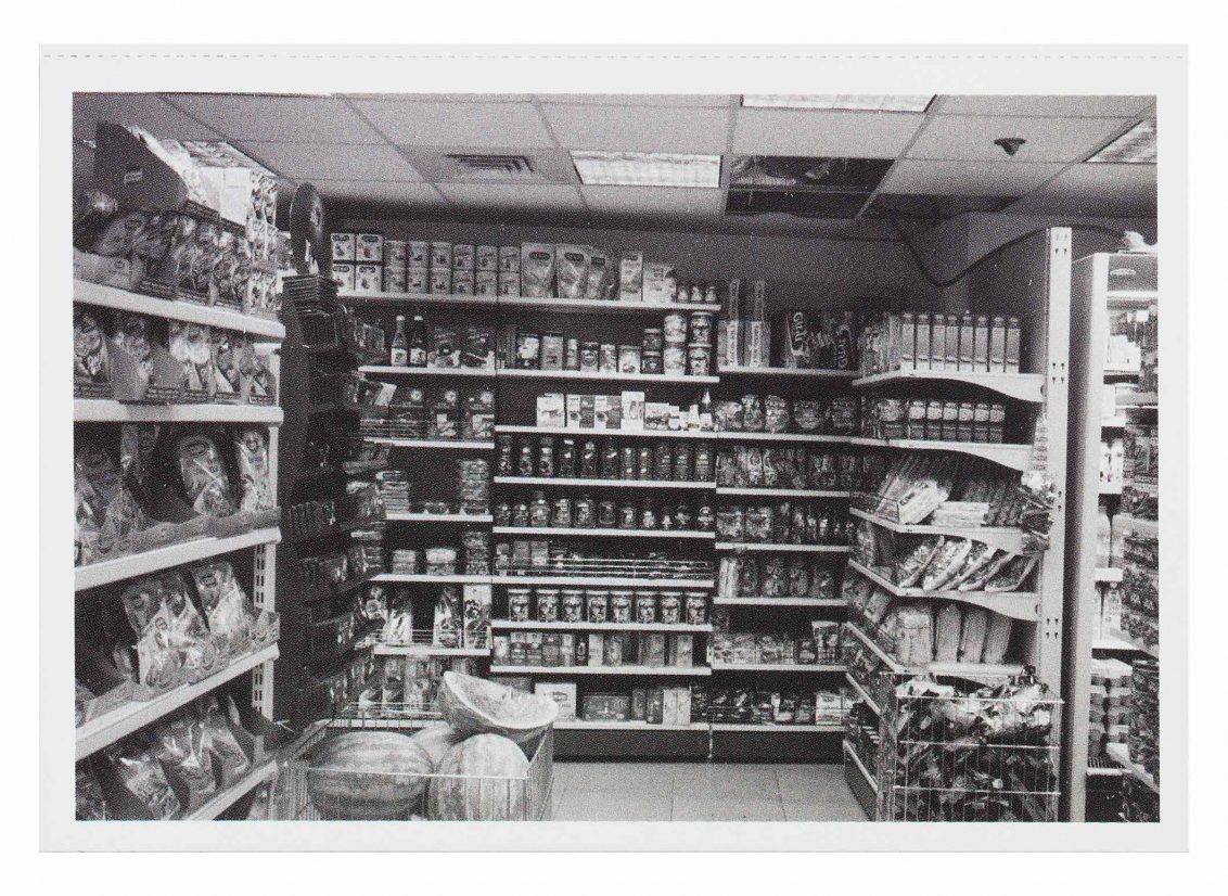 Black and white photograph of a grocery store aisle, a pile of watermelons is surrounded by boxes of food and snacks that line the shelves