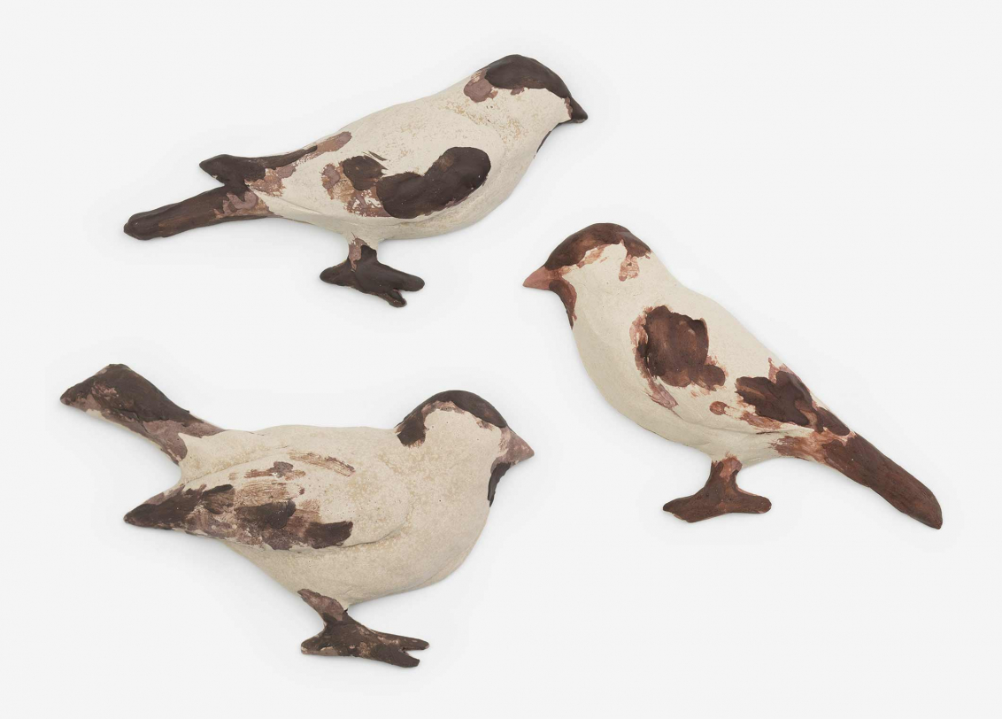 Three sculptures of brown and white birds
