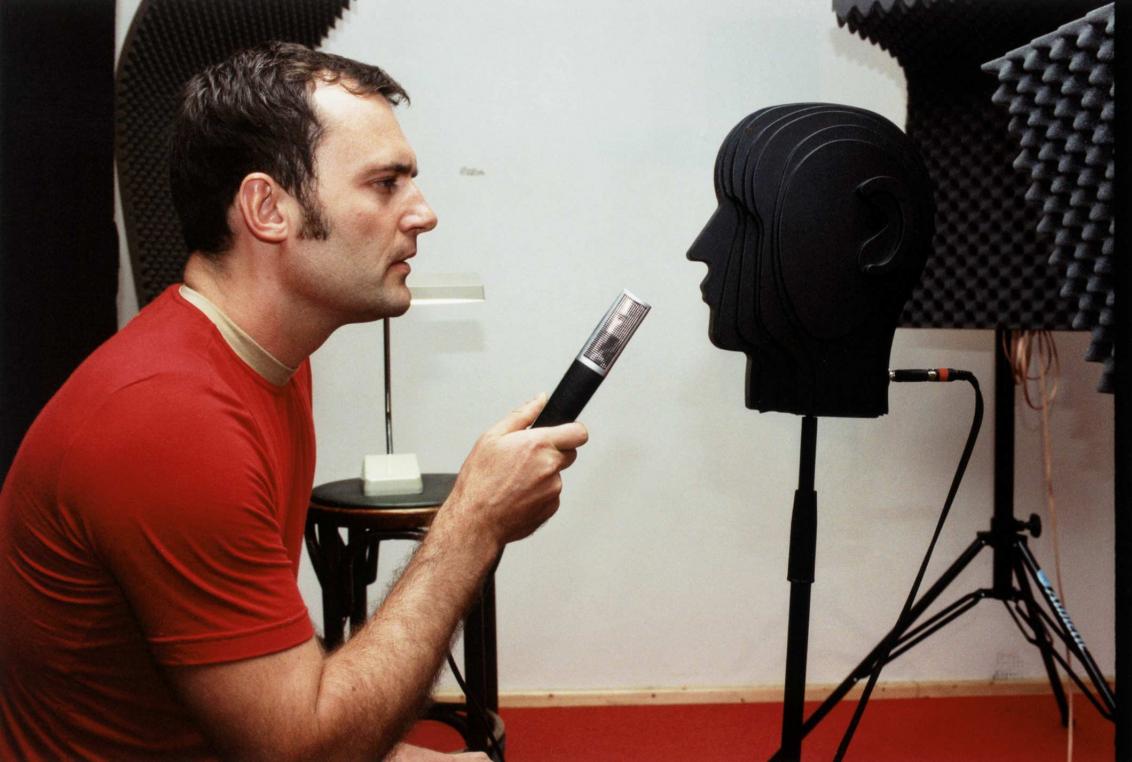 Mann mit rotem T-Shirt im Profil, in der Hand hält er ein Mikrofon