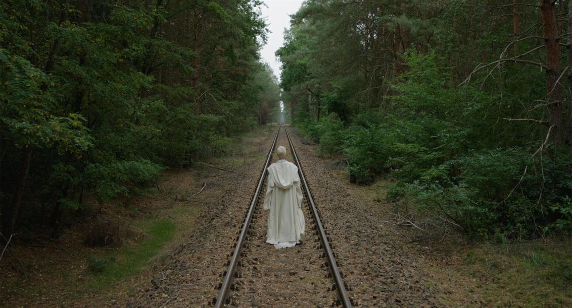 Das Standbild zeigt eine Person von hinten, die mit einer weißen Kutte bekleidete ist. Die Person folgt Eisenbahnschienen, die schnurgerade durch einen Wald führen