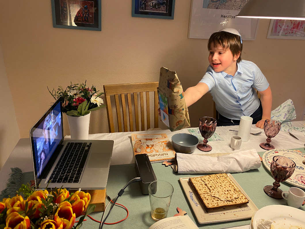 A boy with kippah holds a brown paper bag into the camera from a laptop.