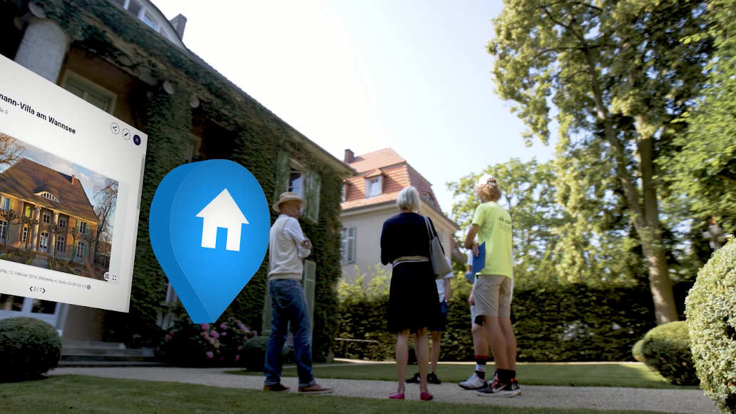 Five people stand in front of a villa. At the left edge of the image a browser window is visible with a photo and some text cut off—next to it is a blue pin with a white house-symbol.