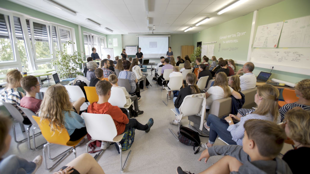 Young people and adults sit on rows of chairs in a large room listening to three young people who are speaking in front of a projector screen.