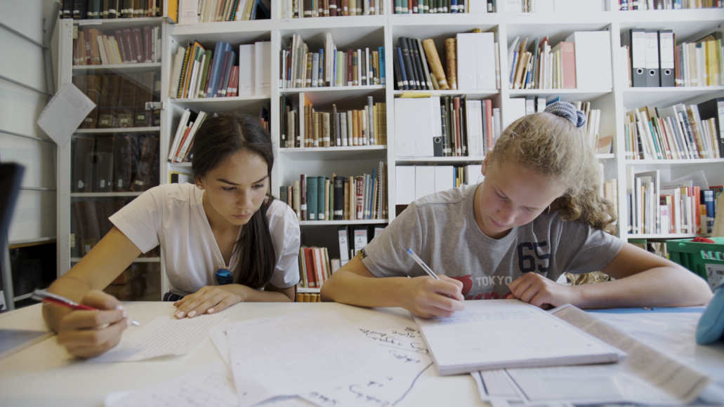 Two young people sit at a table and write with pens in a notebook behind a shelf at the library of the Steglitz Museum.