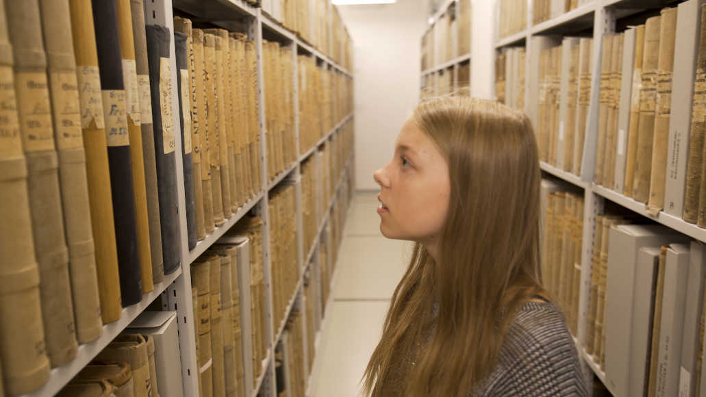 A girl stands in a room in the Brandenburg Main State Archive between shelves of old books.