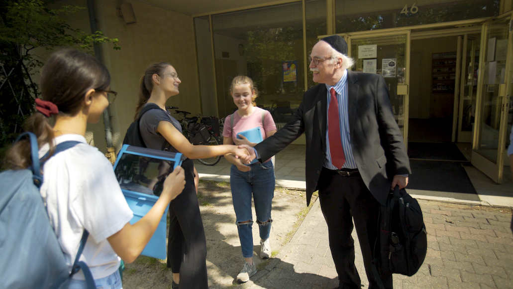 Rabbi Professor Andreas Nachame stands with the young people in front of the entrance to a building and shakes one girl's hand.