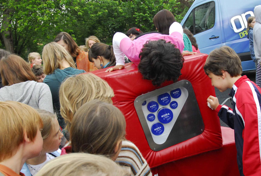 Children gather around and on the mobile exhibition cubes. Inside they discover different-sized Nivea containers.