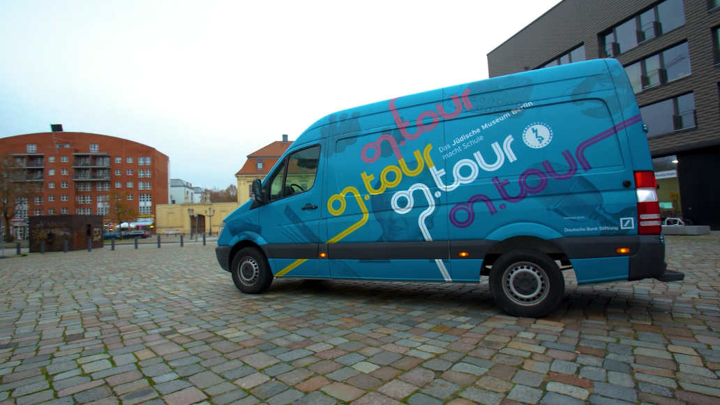 The blue on.tour bus is parked on a cobbled square. The words