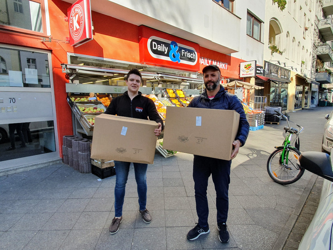 Two men stand in front of a grocery store with an orange outer wall and each hold a moving box in their hands.