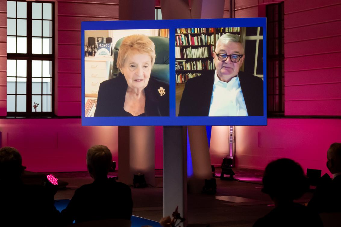 Madeleine Albright und Joschka Fischer sind auf einer Leinwand per Video-Call zugeschaltet