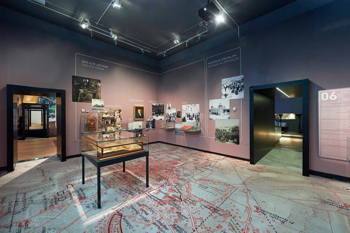 Ausstellungsraum mit historischen Fotografien und Vitrinen