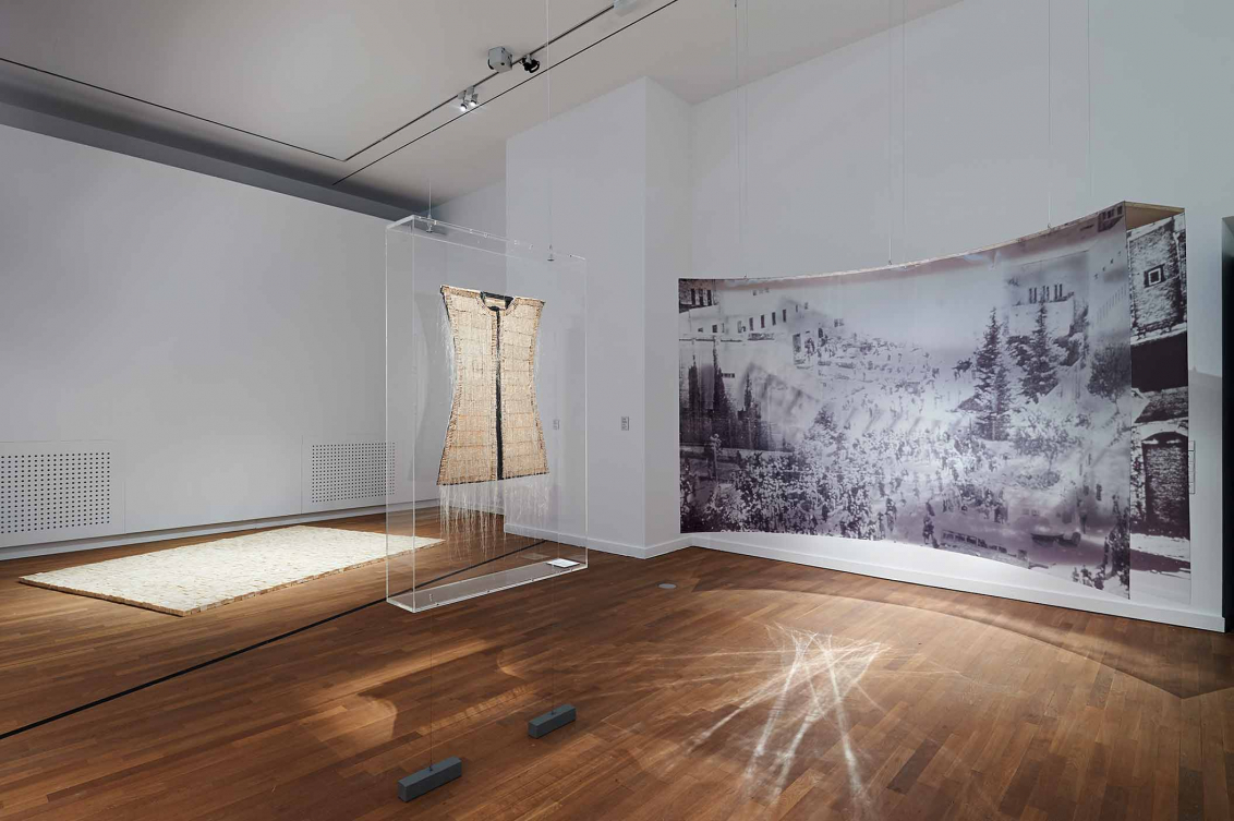 Vor einer Wand hängt eine gebogene Installation aus einer Schwarzweiß-Fotografie, daneben ist eine Vitrine, die ein Kunstwerk enthält, das wie ein ärmelloses Oberteil wirkt. Im Hintergrund ist am Boden eine weiße Fläche zu sehen