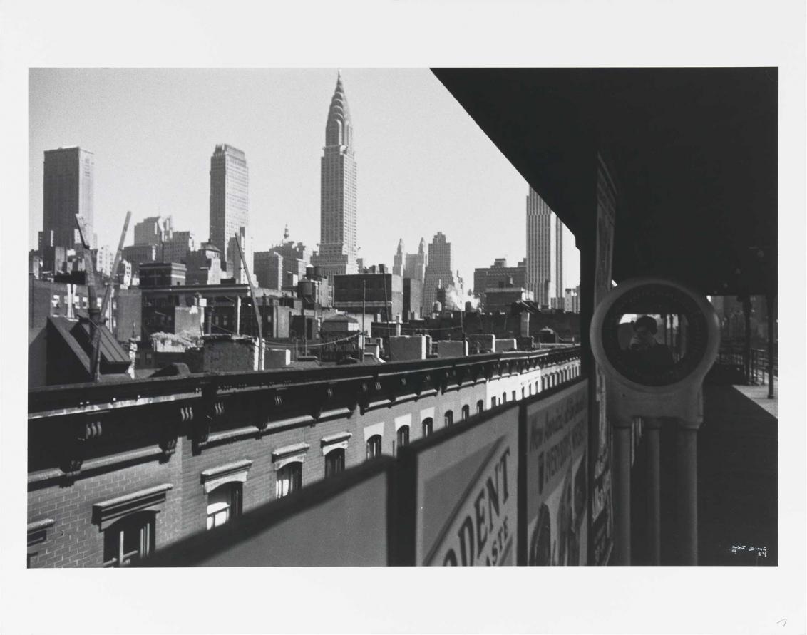 Häuser und Hochhäuser, ein Bahnsteig, auf ihm ein Spiegel, in dem die Fotografin mit ihrer Kamera zu sehen ist.