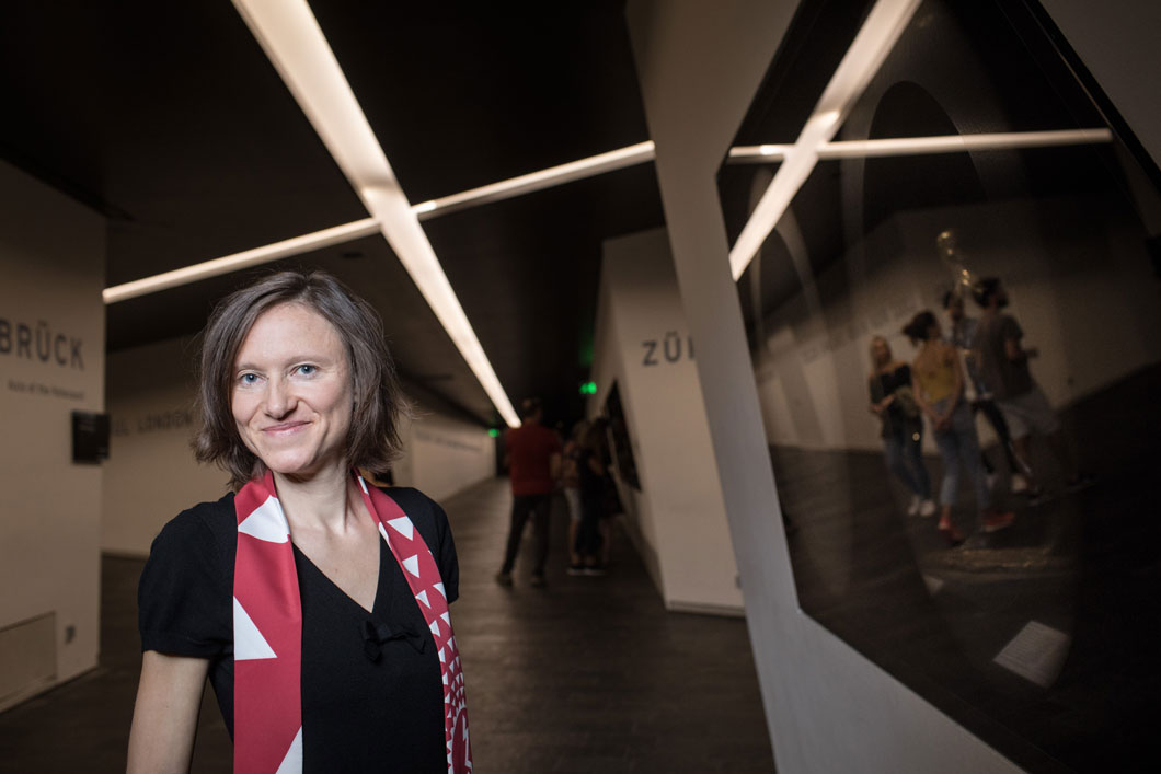 A woman stands in front of a showcase in the axles of the Libeskind building