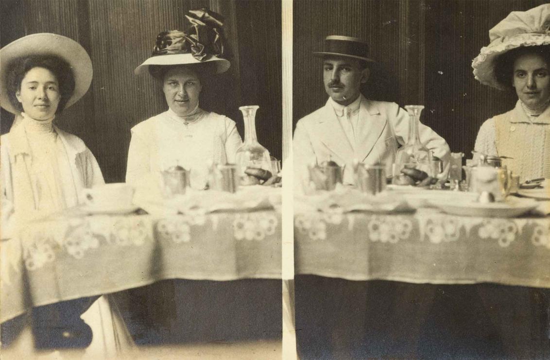 Schwarz-Weiß-Foto von vier jungen Personen an einer gedeckten Tafel. Alle tragen Hüte und blicken kess in die Kamera