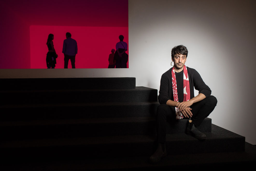 A young man sits on the stairs leading to the installation Ganzfeld Aural by James Turrell.