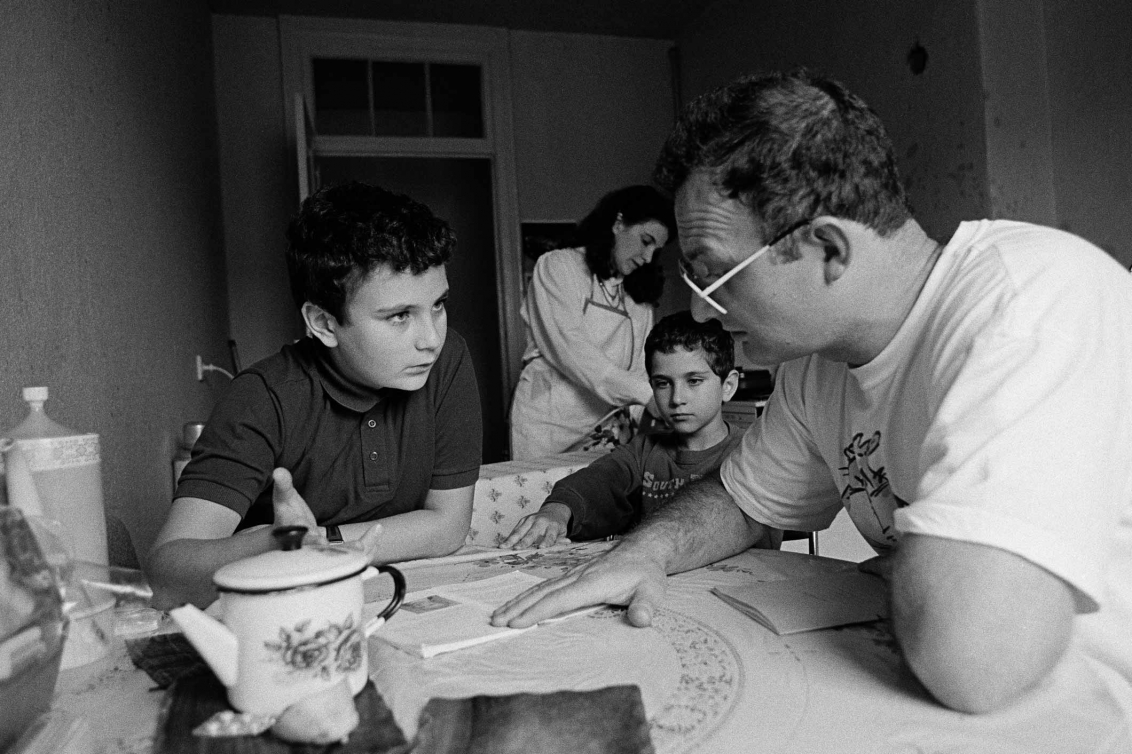 Black and white photo of a man wearing glasses talking to a young boy at a small kitchen table, the man points to a book at the table and the young boy raises his hand as if to ask a question
