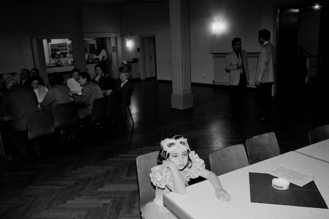 Ein verkleidetes Mädchen sitzt allein an einem Tisch in einem Festsaal, im Hintergrund Erwachsene in Gruppen im Gespräch (Schwarz-Weiß-Foto)