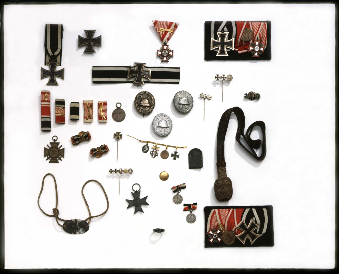 Assortment of objects including badges and pin, many of which have the Iron Cross