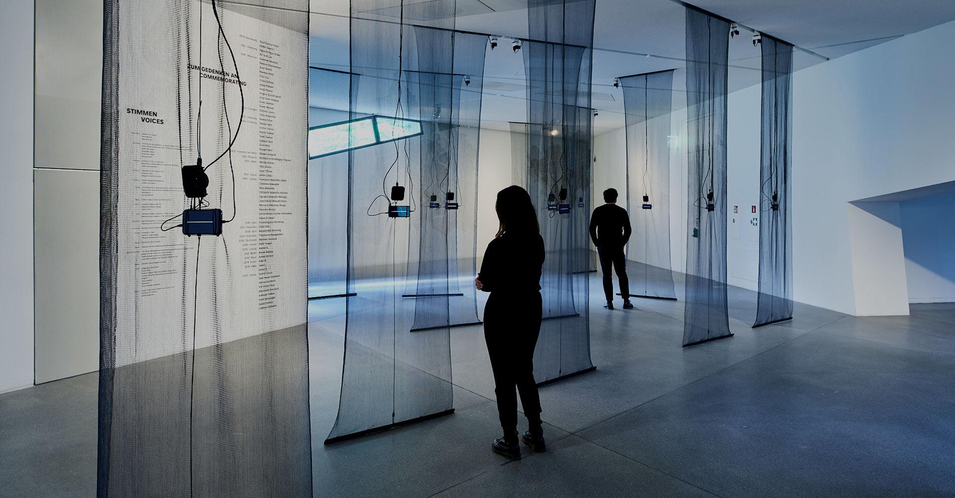 Raumansicht der Ausstellung mit Besucher:innen, von der Decke hängen schwarze durchsichtige Stoffbahnen, an denen je ein Smartphone mit Soundwellen auf dem Display befestigt ist
