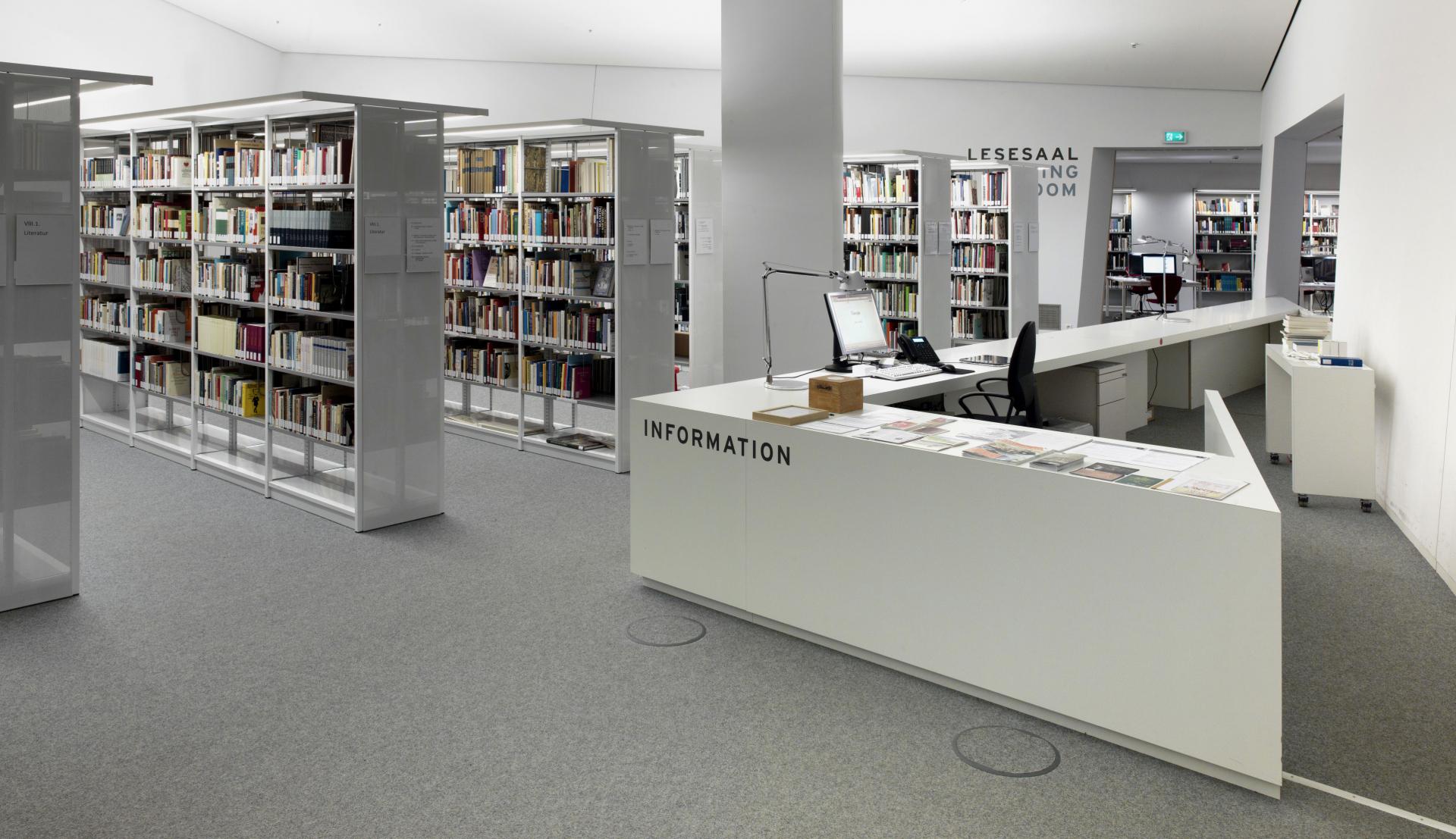 Helle Räumlichkeit, in der Innenausstattung dominiert durch spitze geometrische Formen im Stil des Libeskind Museumsgebäude mit Bücherregalen und Informationstheke