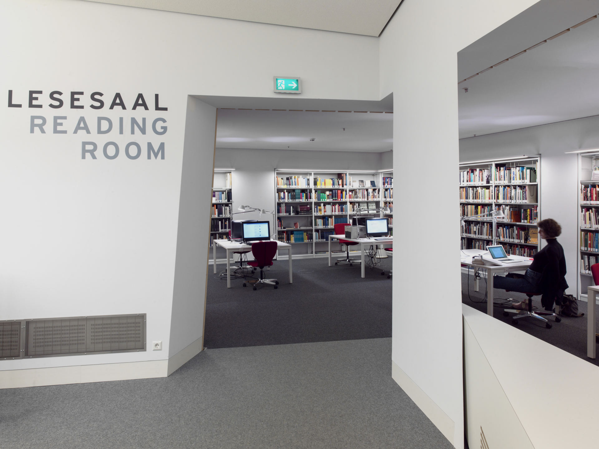 Passage from the reading room to the work area, a woman sits at one of the computers on the tables