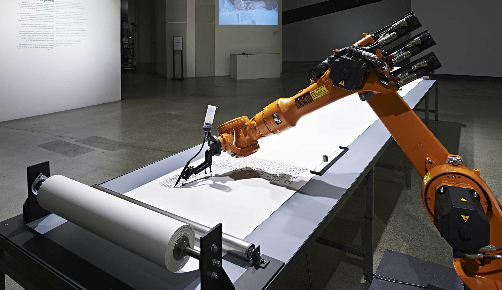A robot arm with a fountain pen is writing on a Torah scroll