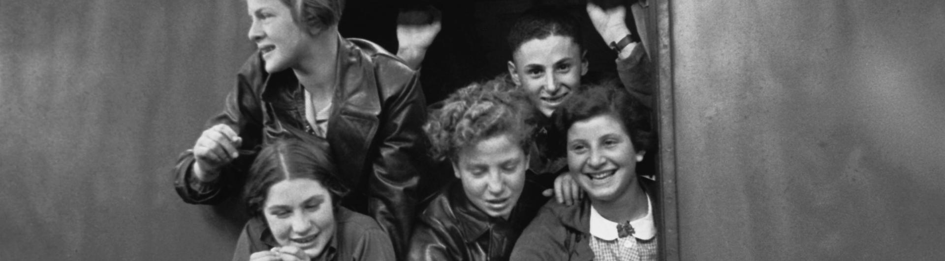 Schwarz-Weiß-Fotografie jugendlicher Jungen und Mädchen, die sich lachend aus einem Zugfenster lehnen
