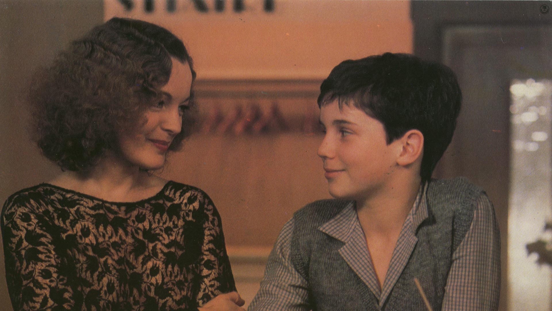 Romy Schneider with a young child, they are both looking at each other and smiling