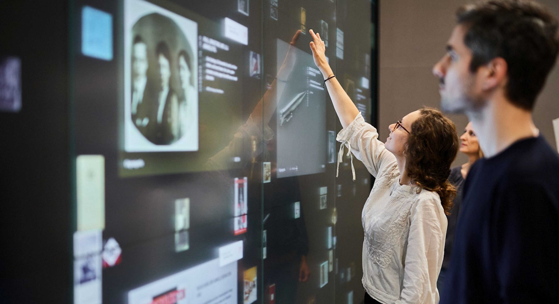 People touch a large touch screen wall that displays documents and objects