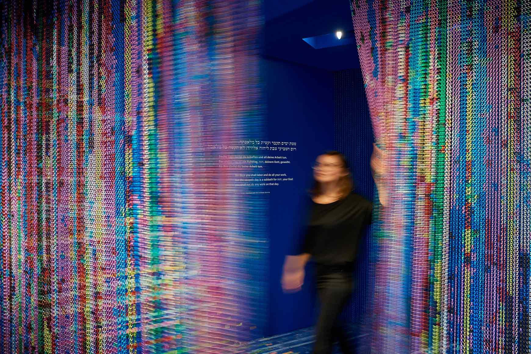 Eine Person geht durch einen bunt glitzernden Vorhang, auf der Wand das Gebot am siebten Tage zu ruhen (auf Hebräisch, Deutsch und Englisch)