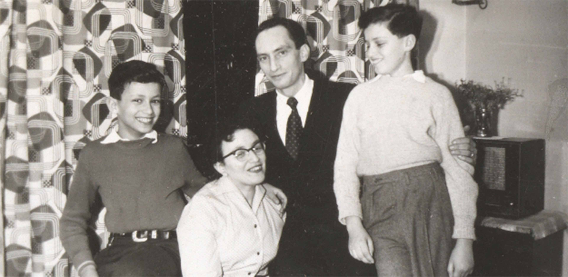 Die Aufnahme zeigt zwei Erwachsene und zwei Kindern in einer Wohnung mit gemusterten Vorhängen. Die beiden Jungs stehen rechts und links neben den Erwachsenen, in der Mitte sitzt eine Frau mit Brille, rechts neben ihr befindet sich ein Mann im Anzug.