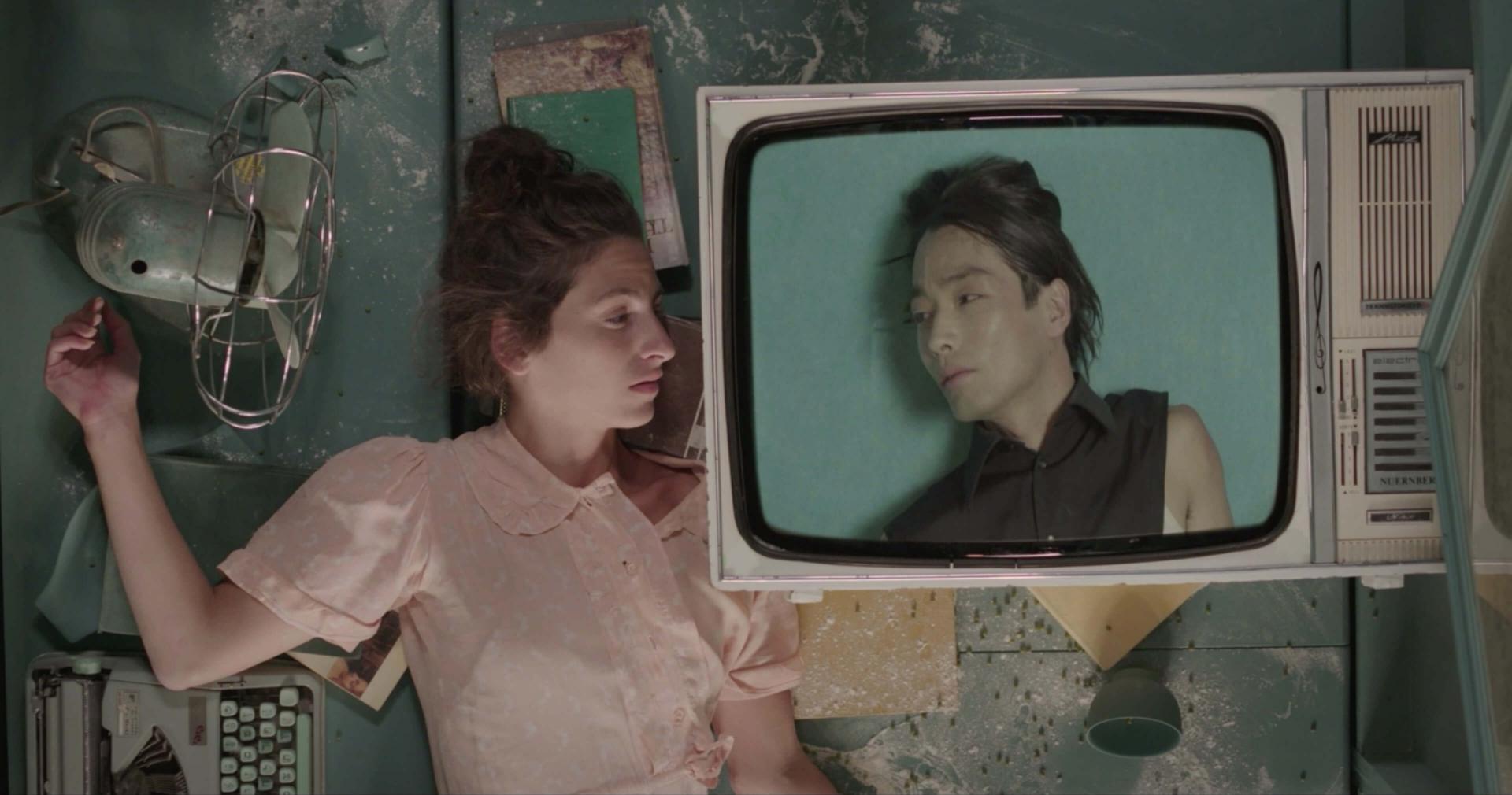 Frau liegt neben Fernseher, auf dessen Bildschirm ein Mann ist, der die Frau anschaut