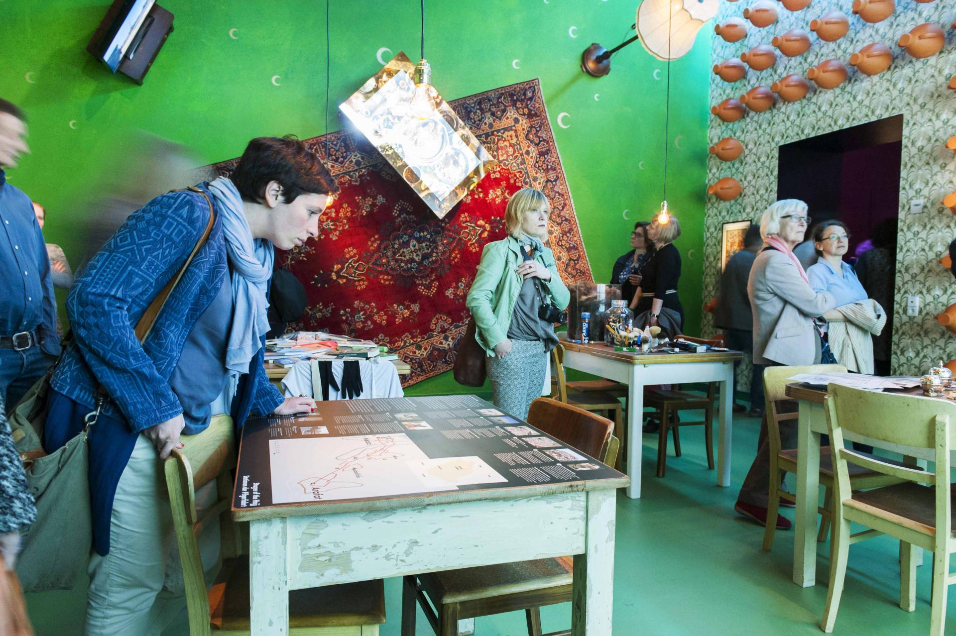 Mehrere Personen beim Betrachten von Objekte in einem vollen, grünen Ausstellungsraum