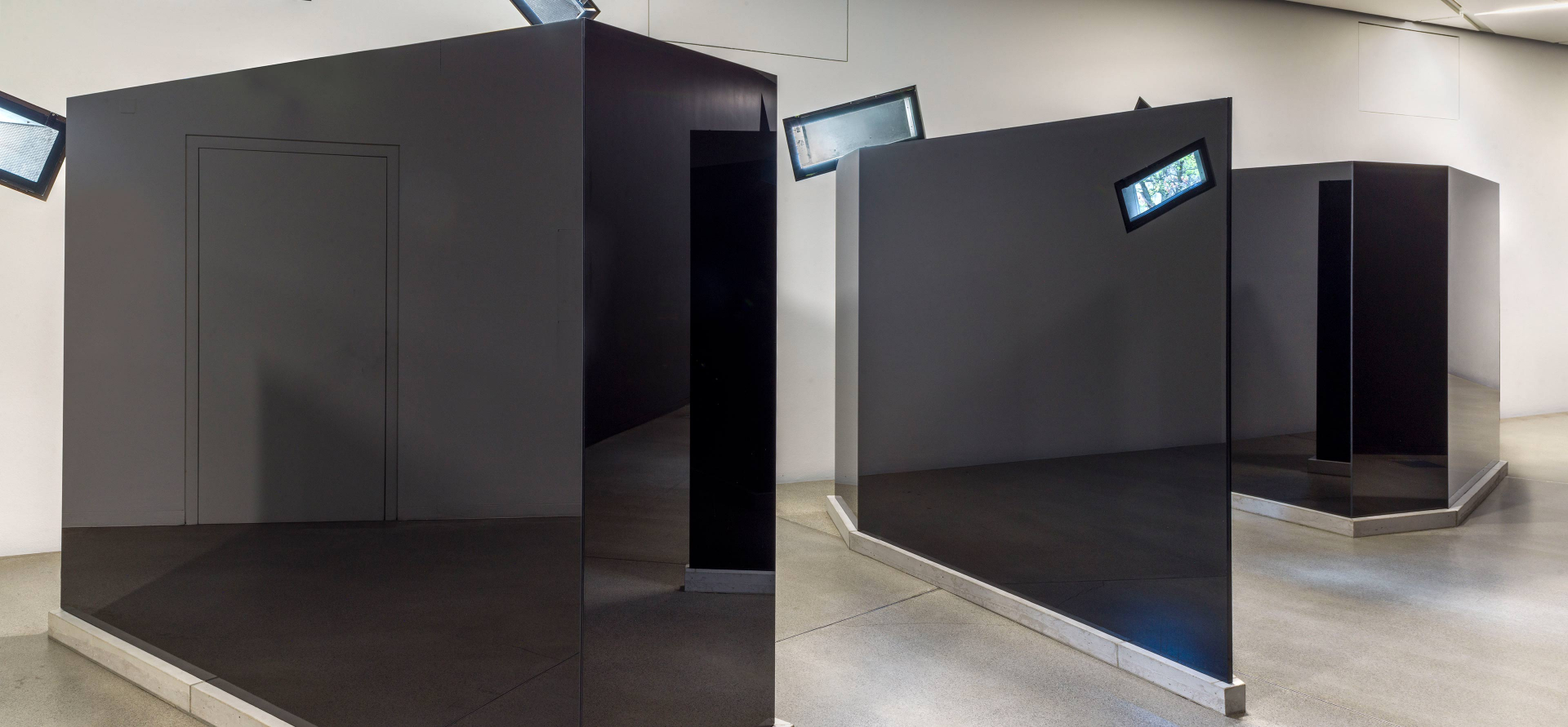 Three trapezoidal black-glass sculptures