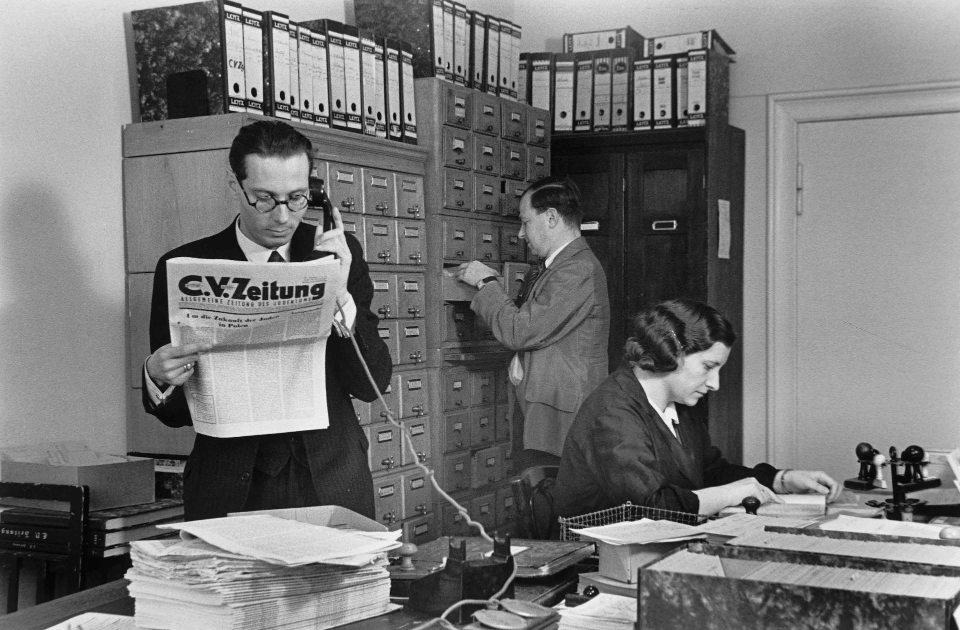 Ein Mann im Anzug liest im Stehen die C.V.-Zeitung und telefoniert dabei, im Hintergrund eine Frau am Schreibtisch und ein Mann am Aktenschrank