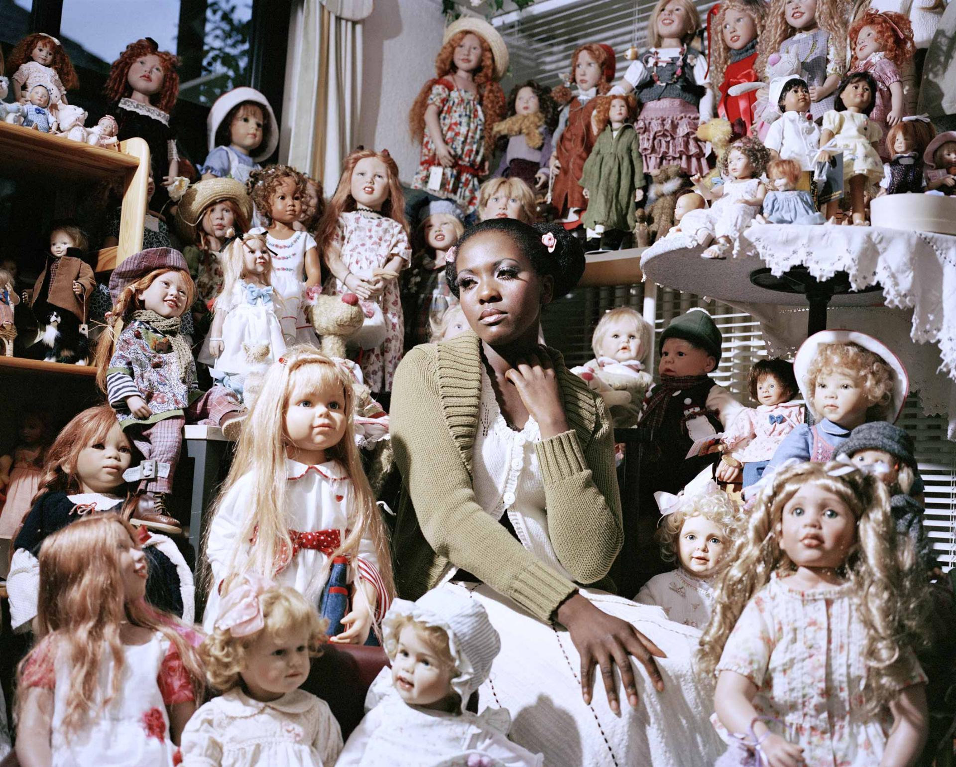 Junge schwarze Frau in weißem Kleid, umringt von unzähligen weißen Puppen