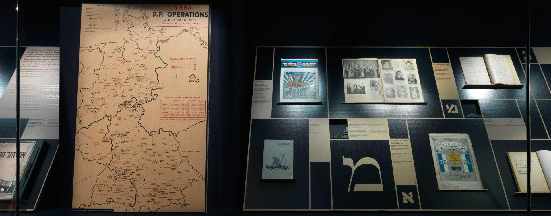 Eine Vitrine mit einer Deutschlandkarte, auf der DP-Lager verzeichnet sind, verschiedenen Publikationen und hebräischen Lettern in verschiedener Typografie
