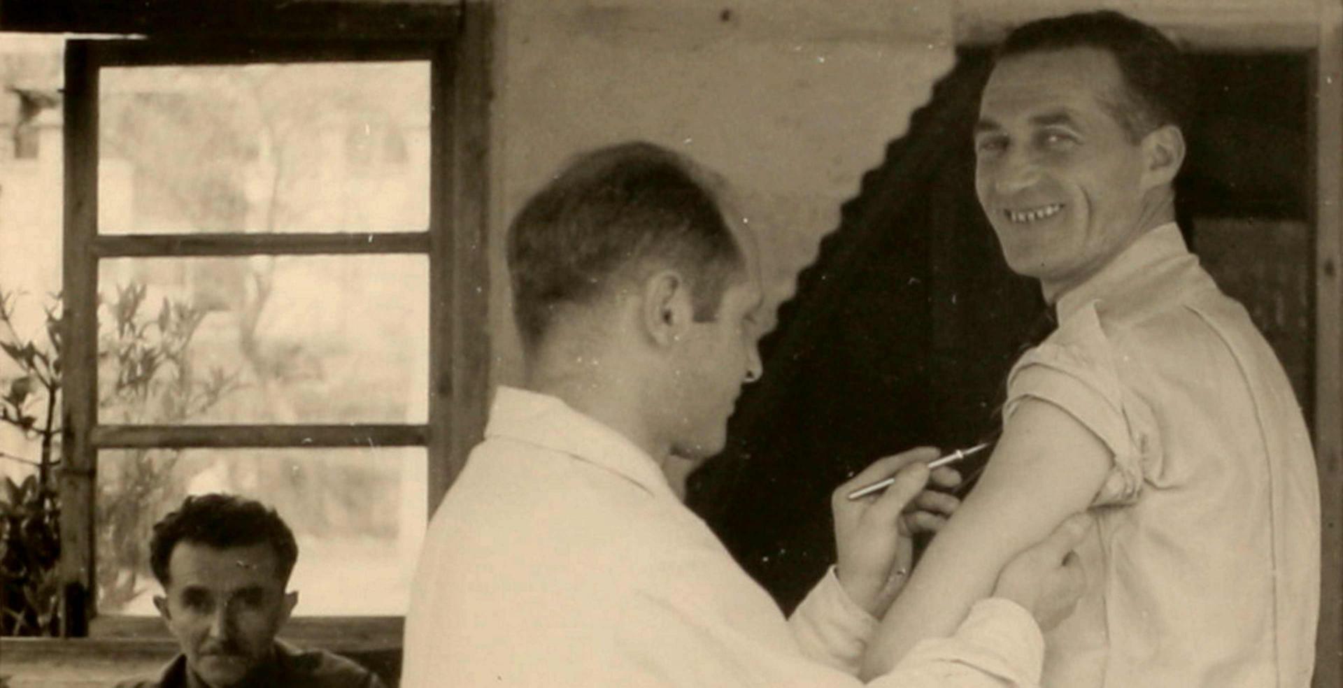 Schwarz-weiß-Foto eines Mannes, dem ein anderer Mann ein Skalpell an den Oberarm hält und der in die Kamera lächelt