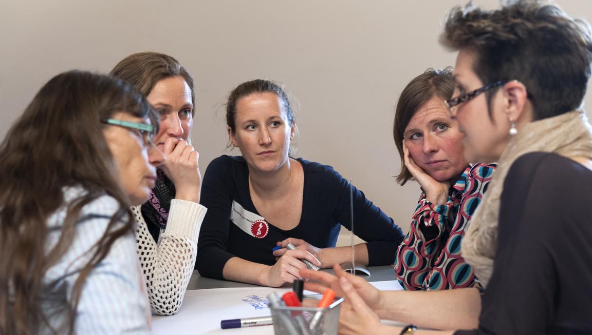 Fünf Frauen im Gespräch am Tisch